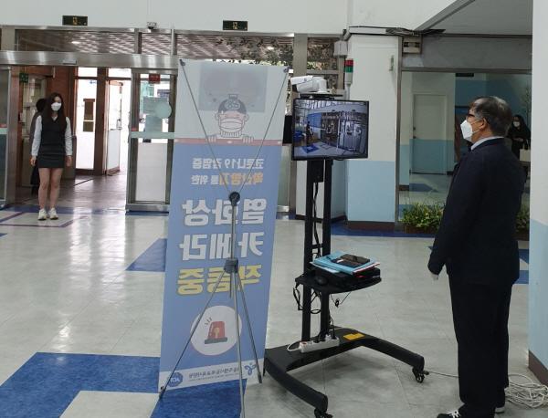 중앙현관 1개소만 개방해 열화상 카메라로 전학생의 발열상태를 검사하고 있다.