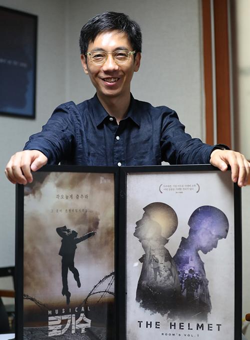 정인석 아이엠컬처 대표가 대표작 '로기수', '헬멧'을 설명한 후 포스터와 함께 기념촬영하고 있다.