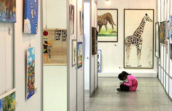 미술 전시회에서 한 어린이가 또래 친구들이 그린 그림을 집중해서 모작하고 있다. (사진=저작권자(c) 연합뉴스, 무단 전재-재배포 금지)