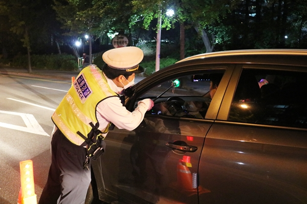 경찰이 비접촉 감지기로 음주단속을 하고 있다.