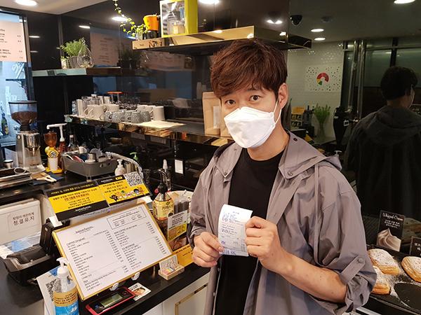 영화배우 유준상씨가 선결제 캠페인에 동참한 후 영수증을 보여주고 있다.(사진=중소벤처기업부 제공)