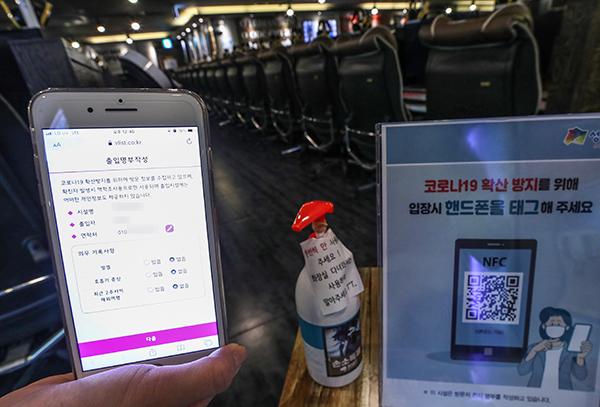1일 서울 성동구의 한 PC방에서 직원이 입구에 비치된 QR코드를 스캔해 방문자의 모바일 전자 명부 작성 과정을 시연하고 있다. (사진=저작권자(c) 연합뉴스, 무단 전재-재배포 금지)