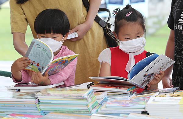 지난 달 25일 오후 세종시 세종시청 야외공간에서 열린 코로나19 위기 극복 '어린이 책 교환 행사'를 찾은 어린이들이 책을 읽고 있다. (사진=저작권자(c) 연합뉴스, 무단 전재-재배포 금지)