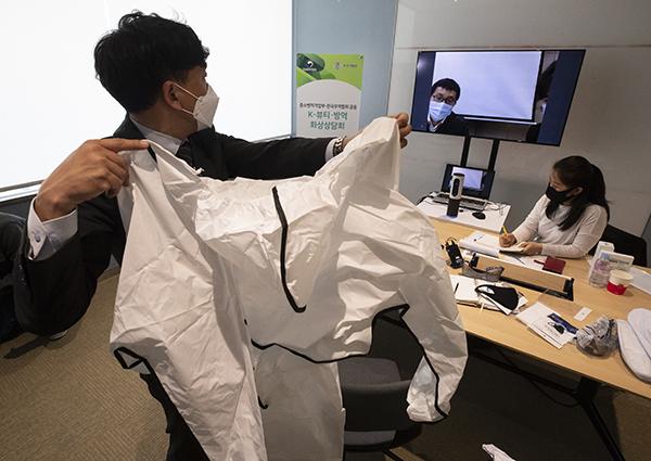 지난 4월 서울 코엑스에서 열린 'K뷰티·방역 화상상담회'에서 한 참가자가 화상연결을 통해 외국 바이어들에게 방호복에 대해 설명하고 있다.(사진=저작권자(c) 연합뉴스, 무단 전재-재배포 금지)