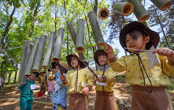 세종시 무궁화유아숲체험원에서 어린이들이 숲속에 매달린 대나무소리통을 두드리며 즐거워하고 있다. (사진=저작권자(c) 연합뉴스, 무단 전재-재배포 금지)