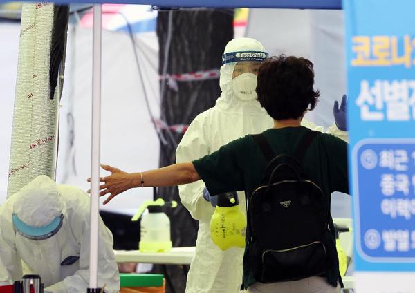서울 한 선별진료소에 의료진과 관계자들이 코로나19 검체 검사를 진행하고 있다.