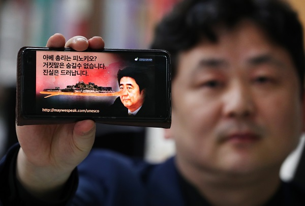 박기태 단장이 '아베 총리는 피노키오?'라는 문구가 담긴 포스터를 보여주고 있다. 이 한 컷은 10개 국어로 제작됐으며, 1주 만에 약 3만명이 '좋아요'를 누르고 13만 명이 구독했다.