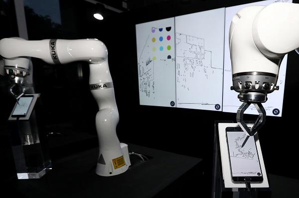 코로나19이후 산업 현장에는 스마트팩토리를 구축해 생산성을 향상시키려는 움직임이 일고 있다. 사진은 휴대전화에 그림을 그리는 로봇 모습. ( 저작권자(c) 연합뉴스, 무단 전재-재배포 금지)