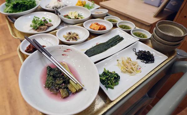 여러가지 반찬을 각자의 그릇에 덜어먹기 위해 개인 찬기와 여분의 젓가락이 준비된 밥상.