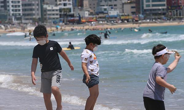 부산 해운대구 송정해수욕장에서 아이들이 마스크를 끼고 물놀이를 하고 있다. (사진=저작권자(c) 연합뉴스, 무단 전재-재배포 금지)