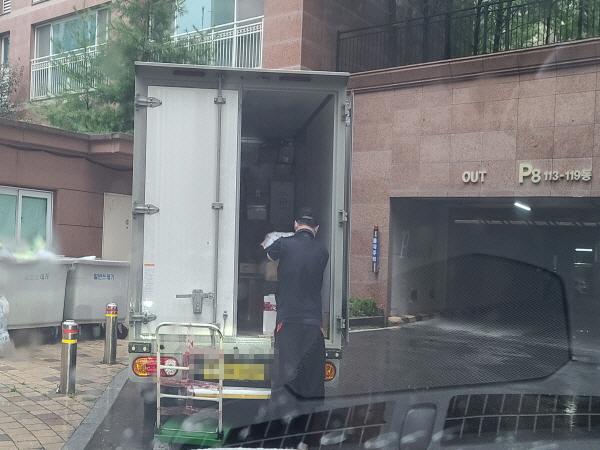 비를 맞으며 택배 상자를 정리하는 택배 기사의 모습에서 열악한 근무여건이 느껴진다.