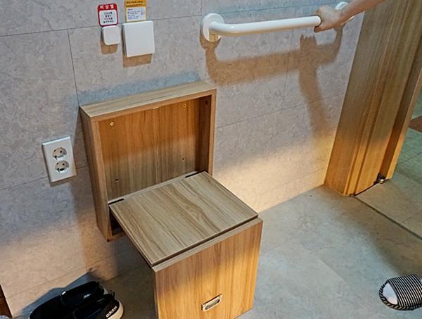 벽에 부착된 나무 판이 열어보니 의자로 바뀌었다. 벽에 부착한 보조 손잡이가 보인다.
