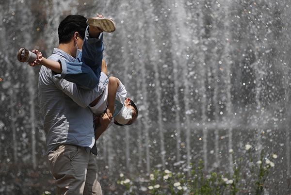 서울 서대문구 홍제천 인공폭포에서 한 어린이가 아빠와 더위를 식히고 있다. (사진=저작권자(c) 연합뉴스, 무단 전재-재배포 금지)