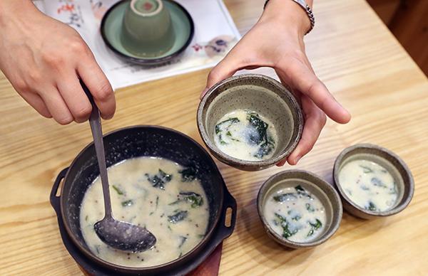 전남 담양지역 안심식당을 찾은 시민이 공용그릇에 나온 음식을 개인 그릇에 나눠담고 있다.