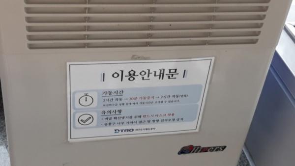 냉풍기 앞에 마스크 착용을 권고하는 안내문구가 있다.