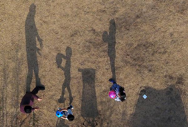 강원 춘천시 공지천 유원지에서 공놀이를 즐기는 시민과 자녀들의 그림자가 햇살에 길게 드리워져 있다. (사진=저작권자(c) 연합뉴스, 무단 전재-재배포 금지)
