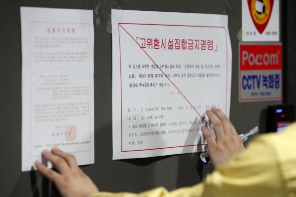 코로나19) 확산 예방을 위해 사회적 거리두기 2단계가 시행된 19일 오후 서울 송파구 일대에서 구청 관계자가 한 코인 노래연습장에 코로나19 확산 억제를 위한 집합금지명령문을 붙이고 있다.