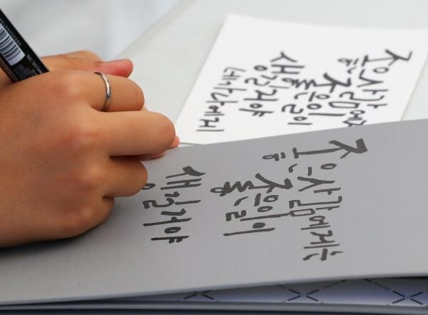 지난해 한글날 서울 광화문광장에서 열린 '한글문화 큰잔치'에서 참가한 어린이가 우리말 글짓기를 하고 있다. 2019.10.9/뉴스1