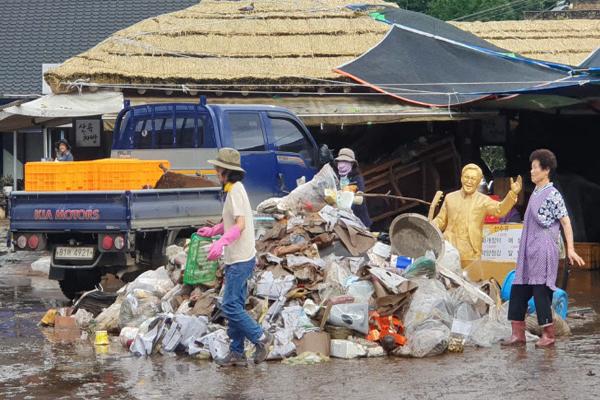 지난 9일 경남 하동군 화개장터에서 상인이 폭우로 침수된 마을을 복구하고 있다. (사진=경남 하동군)