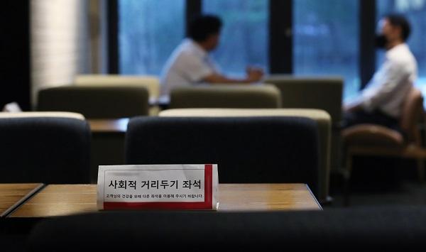 사회적 거리두기 2단계가 조치 중인 21일 서울의 한 카페에서 마스크를 착용한 이용객과 착용하지 않은 이용객이 대화를 하고 있다. (저작권자(c) 연합뉴스, 무단 전재-재배포 금지)