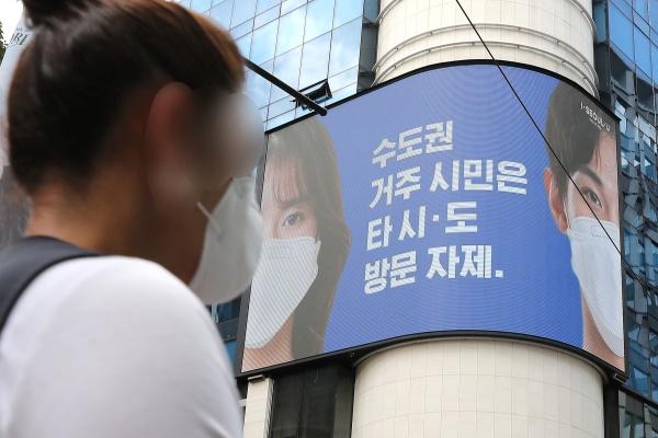 23일 서울 중구 명동거리에서 한 시민이 전광판에 나오는 마스크 쓰기 캠페인 화면 앞을 지나고 있다. (출처=news1)