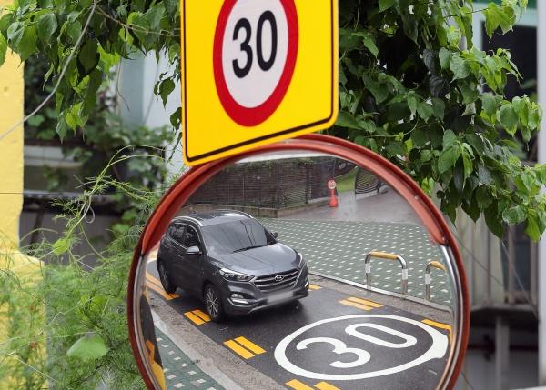 주민이 신고한 어린이보호구역 내 불법 주정차 차량에 과태료 부과가 시행된 3일 서울 종로구 한 초등학교 앞 교통안전거울에 차량이 지나가는 모습이 비치고 있다. 부과되는 과태료는 승용차 기준으로 일반도로의 2배인 8만원이다.(출처=뉴스1)