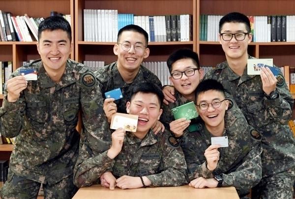 육군 3군단 병사들이 봉급통장을 들어보이며 즐거워하고 있다.(출처=국방부 블로그)