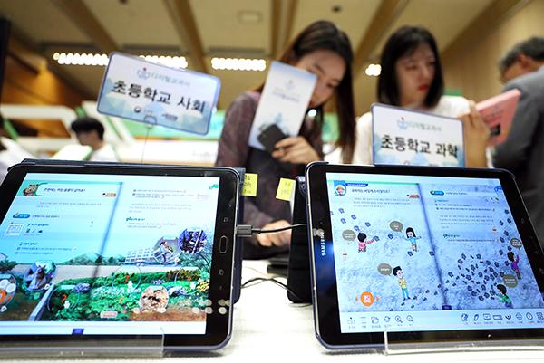2018 이러닝 코리아 국제 박람회를 찾은 관람객이 초등학교 디지털 교과서를 살펴보고 있다. (사진=저작권자(c) 연합뉴스, 무단 전재-재배포 금지)