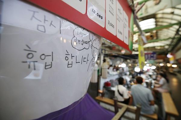 """코로나19 재확산으로 소상공인의 고통이 가중되는 가운데 6일 서울 광장시장의 한 가게에 붙은 휴업 안내문에""""다 함께 이겨냅시다""""라는 응원 문구가 적혀 있다.(저작권자(c) 연합뉴스, 무단 전재-재배포 금지)"""