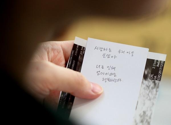 지난 2017년 제12회 임산부의 날 기념행사에서 한 임산부가 캘리그라피 액자에 넣을 문구를 직접 적어 초음파사진과 함께 들고 있다. (저작권자(c) 연합뉴스, 무단 전재-재배포 금지)