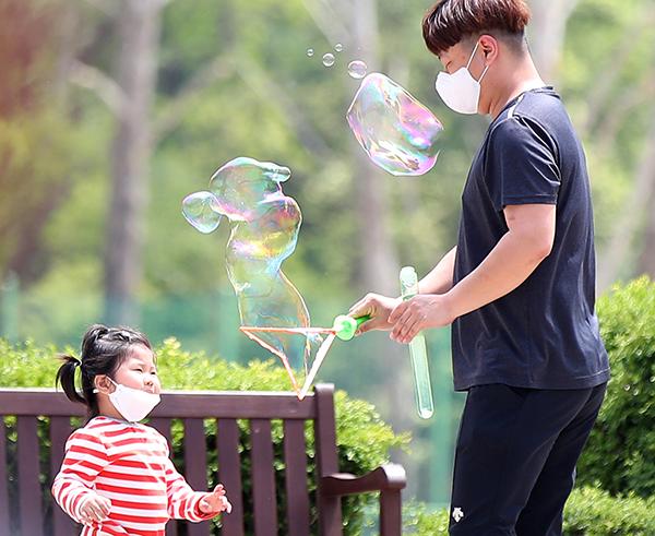 서울 광진구 어린이대공원을 찾은 한 부녀가 비눗방울 놀이를 즐기고 있다. (사진=저작권자(c) 연합뉴스, 무단 전재-재배포 금지)