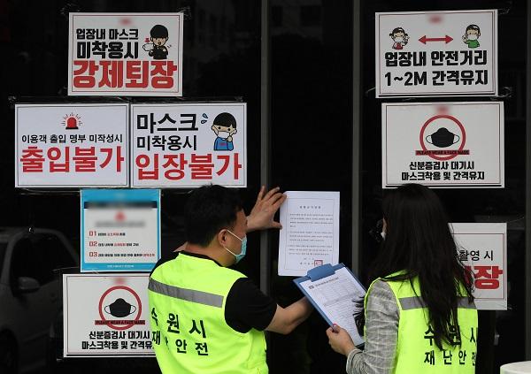 지난 5월 경기도 수원시의 한 클럽에서 공무원들이 코로나19 확산 방지를 위한 집합금지 행정명령서를 붙이고 있다.(사진=저작권자(c) 연합뉴스, 무단 전재-재배포 금지)