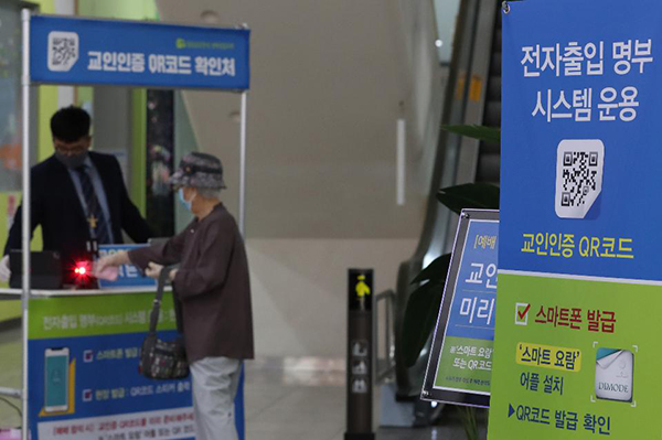 서울 성동구 성락성결교회 교인들이 출입을 위해 QR코드를 확인하고 있다.