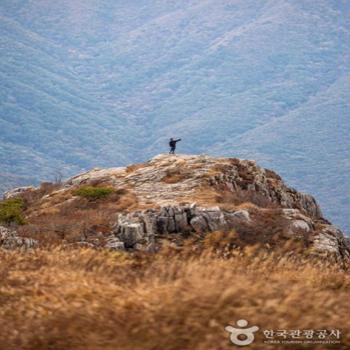 억새 군락지 너머로 우뚝 솟아있는 암벽 구간이 거친 산세의 매력을 뽐냈다