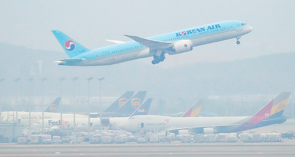 18일 오전 인천국제공항 주기장에 세워진 아시아나항공 여객기 위로 대한항공 여객기가 이륙하고 있다.(사진=저작권자(c) 연합뉴스, 무단 전재-재배포 금지)