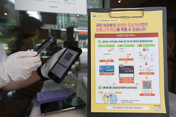 서울의 한 카페에서 직원이 전자출입명부 기록을 위해 출입 손님들의 QR코드를 인식하고 있다. (사진=저작권자(c) 연합뉴스, 무단 전재-재배포 금지)
