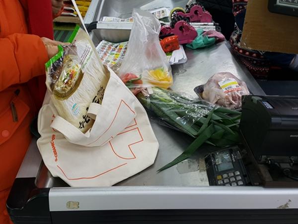 아내가 동네 슈퍼마켓에서 쇼핑한 물건들을 에코백에 담고 있다.