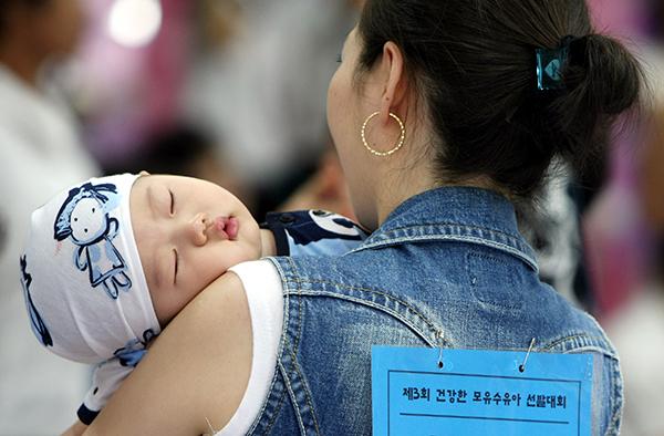 한 아가가 엄마 품에 안겨 곤히 잠들어 있다.