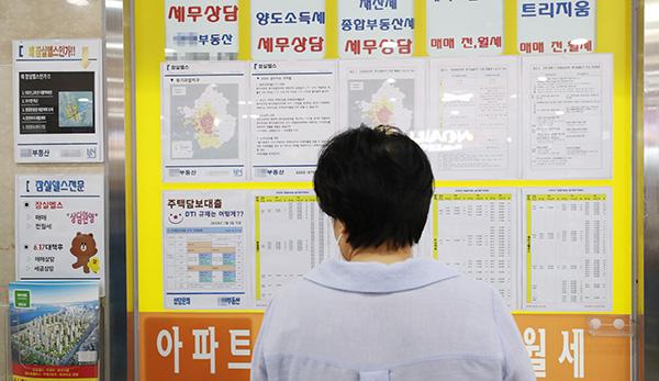 서울 송파구 한 상가 부동산 중개업소에 붙어 있는 부동산 규제 관련 안내문을 시민이 살펴보고 있다.