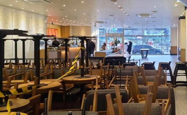 테이크아웃만 가능한 카페의 테이블과 의자가 한쪽에 쌓여 있다.