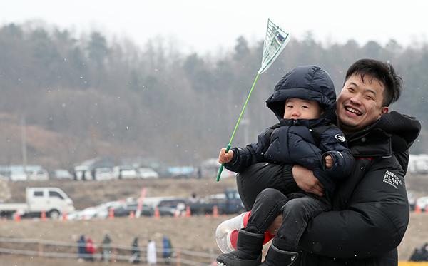 강원 인제군 남면 빙어호에서 아들을 안은 아빠가 낚시터로 향하고 있다.