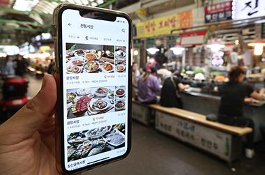서울 광장시장에서 앱을 통해 전통시장 배달 서비스를 이용하는 모습.