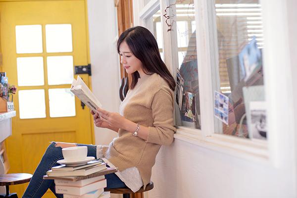 한 여자가 커피 잔을 옆에 두고 책을 읽고 있다.