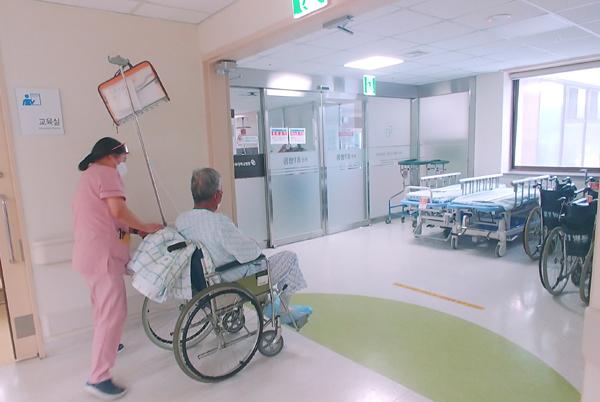 환자를 돌보는 간호사와 휠체어를 탄 어르신.