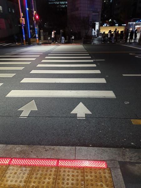 인도와 도로의 경계면을 따라 바닥 신호등이 설치되고 있다.