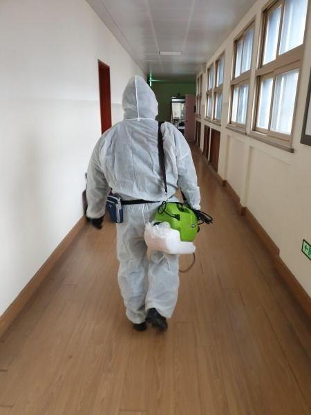 방역 요원이 방역 장비를 들고 교실로 향하고 있다.