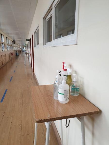복도 바닥에 일방통행 표시가 있고, 교실 앞에 손 소독제가 놓여 있다.