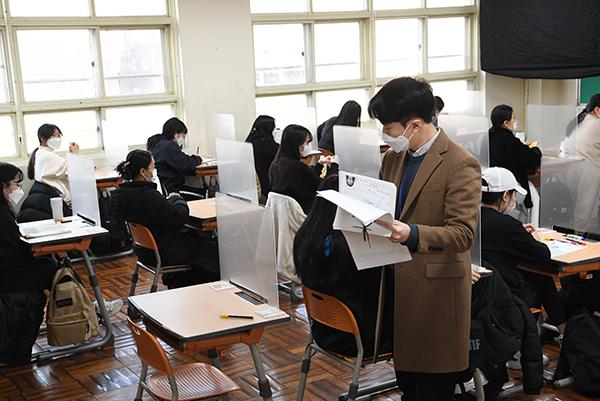 지난해 대학수학능력시험일인 12월 3일 오전 부산 동구 경남여고의 한 시험장에서 감독관들이 수험생 신원을 확인하고 있다.