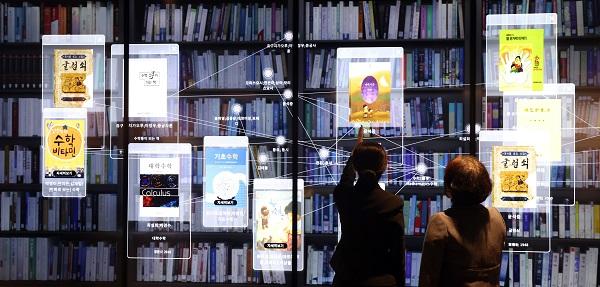 국립중앙도서관 '실감서재(뉴미디어 체험관)' 개관식에 참석한 관람객들이 3D 영상 대형 화면을 통해 수장고를 체험하고 있다.