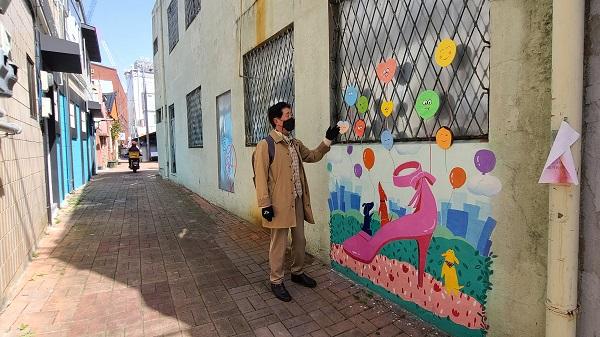 20여 명의 작가가 참여한 수제화거리 벽화를 천광호 작가가 설명하고 있다.